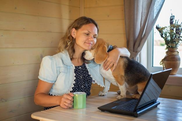 Молодая женщина обнимает собаку бигля, сидящую за столом перед экраном ноутбука