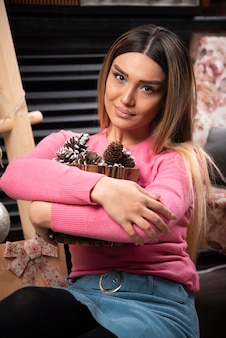 젊은 여자는 집에서 솔방울 양동이를 껴안습니다.