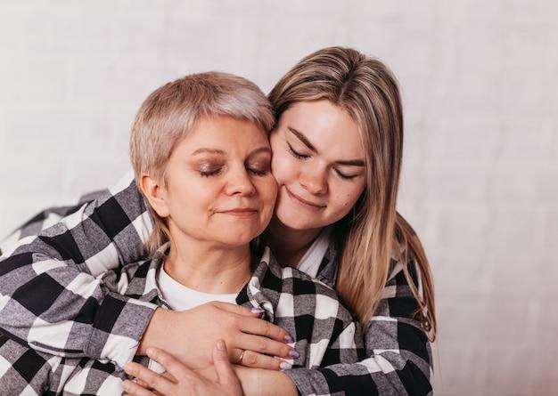 若い女性は優しさで彼女の年配の母親を抱きしめます