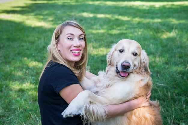 若い女性は公園の芝生の背景に彼女のレトリーバー犬を抱きしめます