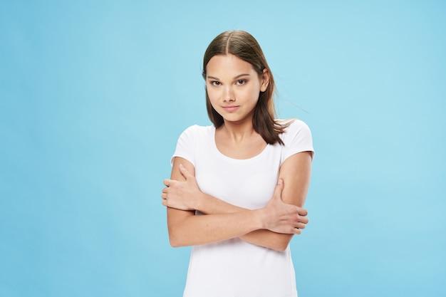 젊은 여성은 파란색 배경과 흰색 티셔츠 모델에 손을 얹고 자신을 껴안습니다.
