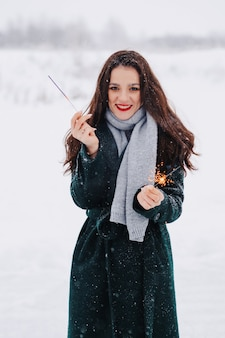 Young woman ice skating outdoors on a pond on a freezing winter day with sparklers in hand