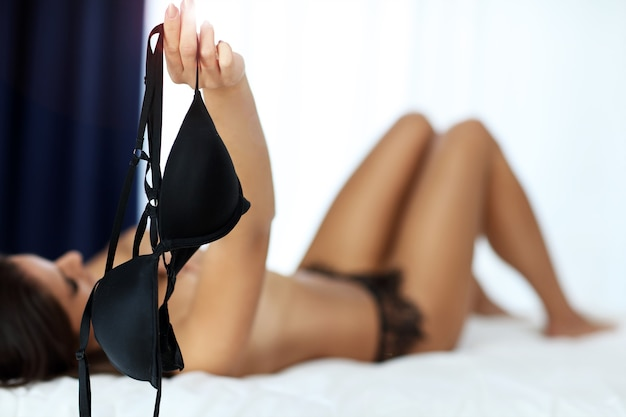 Young woman ilying on bed and holding bra in hand