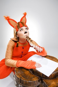 Young woman in image of squirrel writing with quill pen