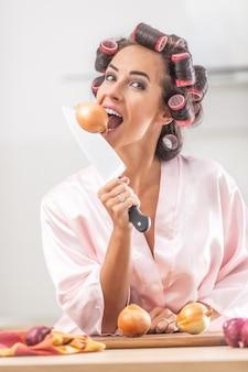 젊은 여성은 손에 칼을 들고 머리에 curlers를 물고 양파를 모방합니다.