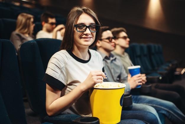 Молодая женщина в очках 3d с попкорном, сидя на сиденье в кино. showtime, просмотр фильмов