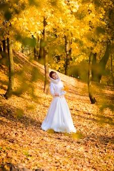 秋の公園で若い女性。白いドレスの葉を持つ女性