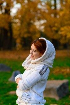 가 공원에서 젊은 여자. 흰 드레스를 입은 잎사귀를 든 여인