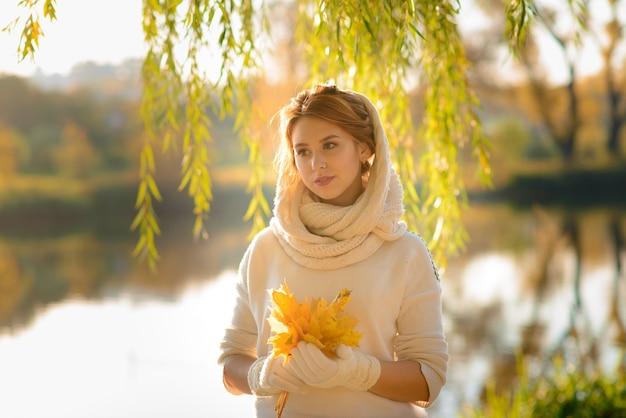 가 공원에서 젊은 여자. 잎을 가진 여자입니다.