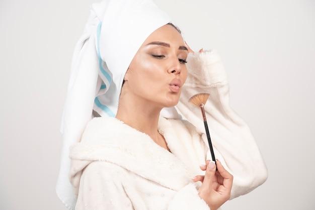 メイクブラシで吹くバスローブの若い女性