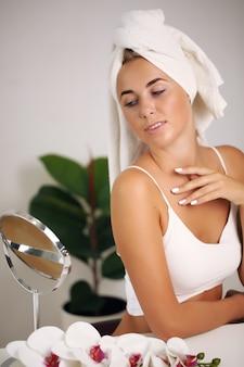 バスローブの若い女性は、バスルームに美しさをもたらします