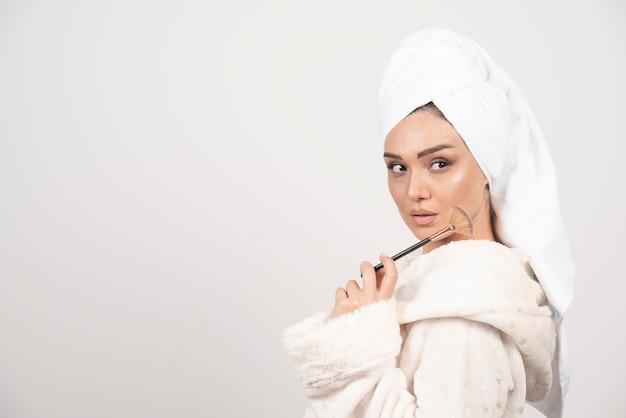 메이크업 브러쉬를 들고 목욕 가운에 젊은 여자