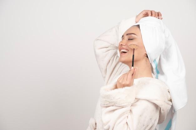 メイクブラシを保持しているバスローブの若い女性