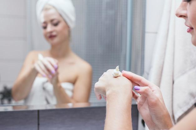 浴室の若い女性はタオルで美しさと健康を高めるために化粧品の手順を保持します