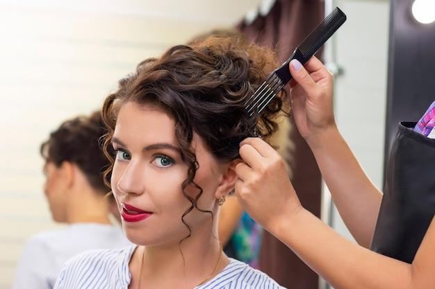 Молодая женщина в салоне красоты. парикмахер делает прическу