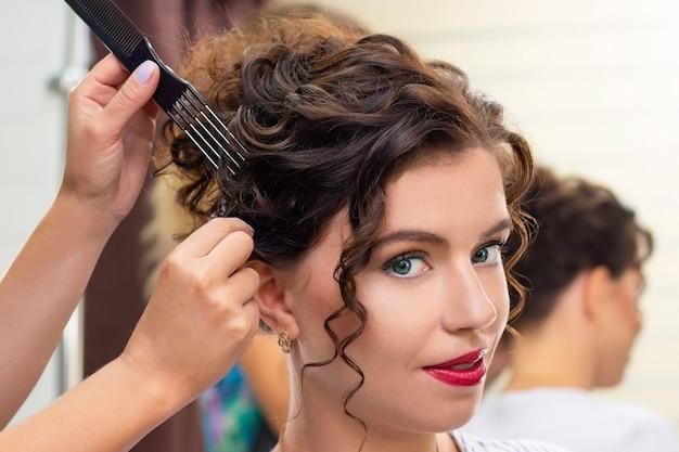 美容院の若い女性。美容師は髪型を作ります