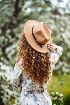 베이지 색 모자와 흰색 드레스를 입은 젊은 여성이 꽃이 만발한 나무 근처의 거리에있는 공원에서 그녀와 함께 서 있습니다. 여자의 곱슬 머리에 사과 나무의 꽃.
