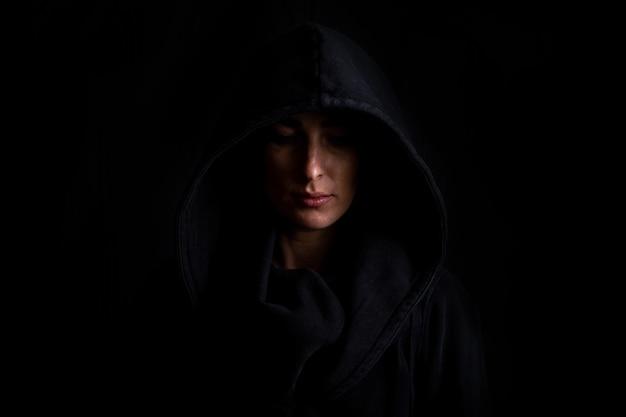 어두운 검은 배경에 검은 후드에 젊은 여자.