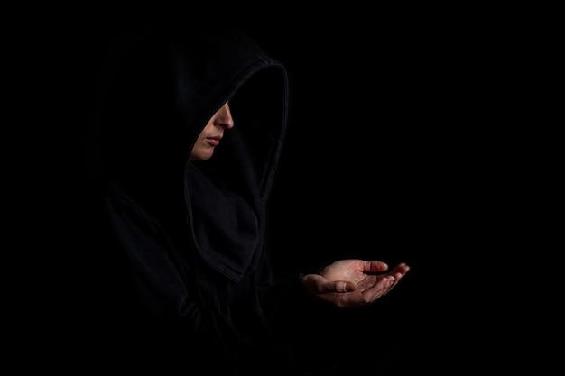 어두운 검은 배경에 뻗은 손으로 검은 후드에 젊은 여자.