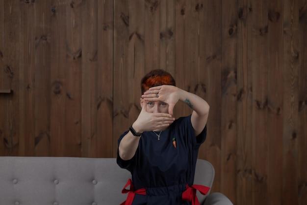 회색 소파에 그녀의 손으로 사각형 모양을 만드는 스튜디오에서 포즈를 취하는 파란 드레스에 젊은 여자.