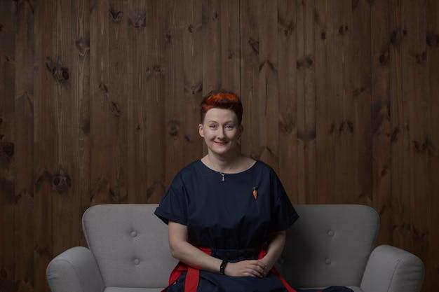 灰色のソファのスタジオでポーズをとる青いドレスを着た若い女性。