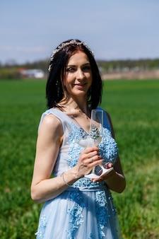 Молодая женщина в синем длинном платье держит в руках стакан