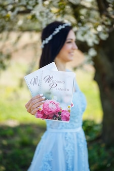 Молодая женщина в синем длинном платье держит в руках свадебный планер