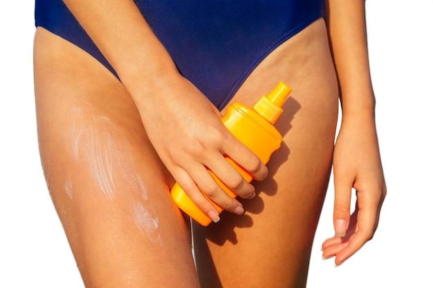 プラスチック製のオレンジ色のパッケージスプレーボトルを保持し、彼女の体に日焼け止めを置く青い水着の若い女性。白い背景の上のビーチの分離の夏の太陽紫外線保護spf