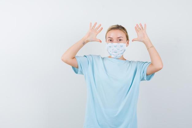 Молодая женщина в синей футболке с медицинской маской