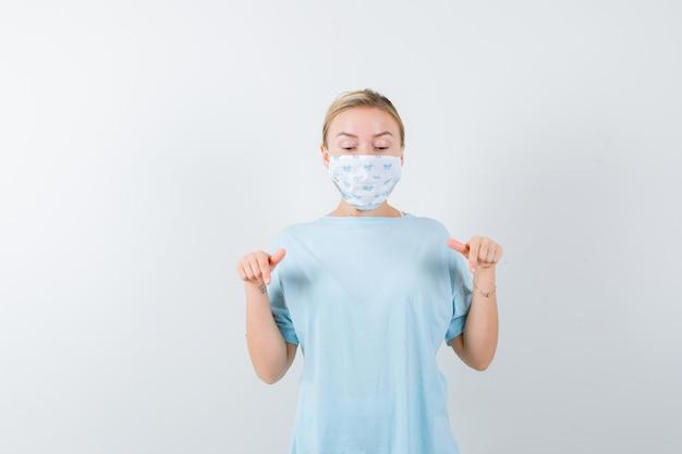 의료 마스크가 있는 파란색 티셔츠를 입은 젊은 여성