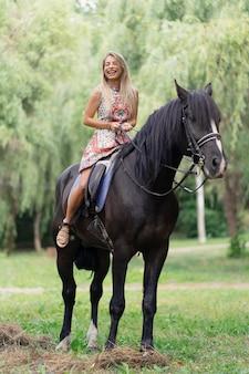 黒い馬に乗って明るくカラフルなドレスの若い女性