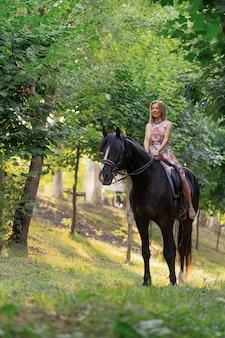 Молодая женщина в ярком красочном платье верхом на черной лошади