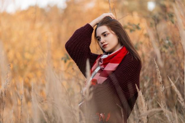 Молодая женщина в бордовом вязаном свитере и клетчатом шарфе позирует в парке