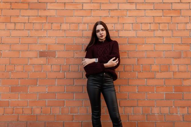 Молодая женщина в бордовом свитере и черных кожаных штанах стоит в городе у кирпичной стены
