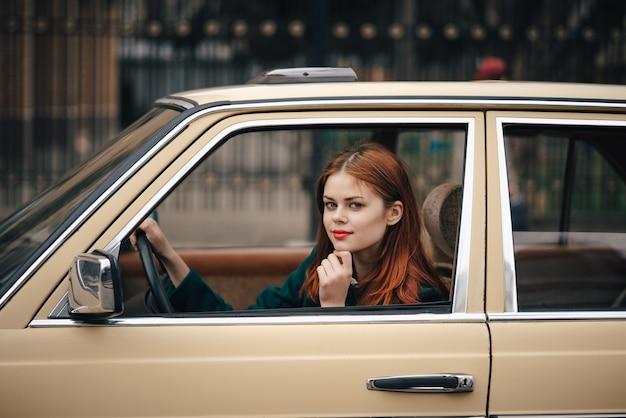 車、ドライバー、乗客、レトロな車の若い女性