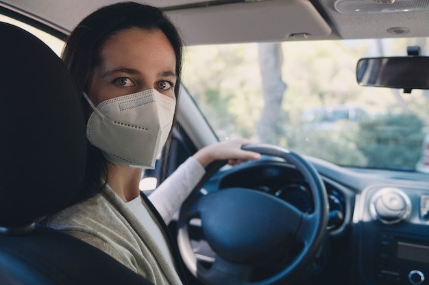 Covid-19 유행성 기간 동안 보호 마스크를 쓰고 차에있는 젊은 여성