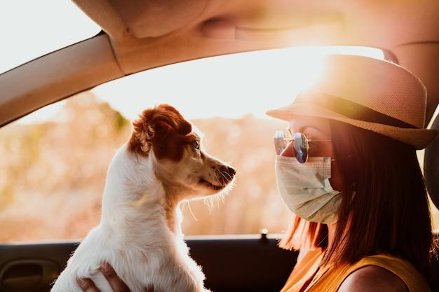 彼女のかわいい小さな犬を抱きしめる防護マスクを着ている車の中で若い女性