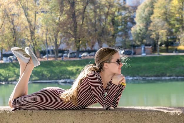 Молодая женщина в вскользь платье и солнцезащитные очки, отдыха на свежем воздухе в теплый осенний день.