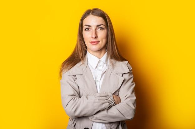 Молодая женщина в пальто скрестила руки на груди на желтом фоне