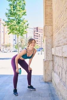 しゃがみ姿勢で休むと笑顔の若い女性は、都会の場所で水の健康的なライフスタイルの概念の夏のトレーニングのボトルを保持