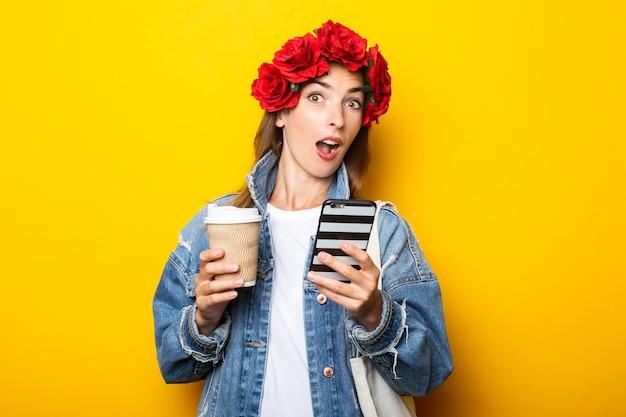 Молодая женщина в джинсовой куртке и венке из красных цветов на голове держит бумажный стаканчик с кофе и телефон на желтой стене.
