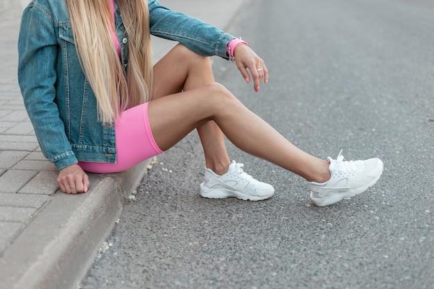 흰색 운동화에 분홍색 세련된 반바지에 데님 재킷을 입은 젊은 여성이 도시의 보도에서 쉬고 있습니다. 트렌디 한 여름 옷에서 여성 다리의 클로즈업. 세련된 모습. 미국식.