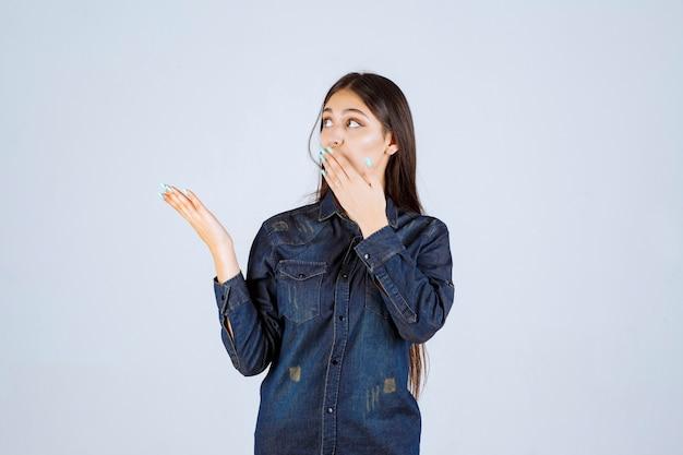 顔の感情で左側を指しているデニムシャツの若い女性