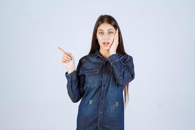 얼굴 감정 왼쪽을 가리키는 데님 셔츠에 젊은 여자