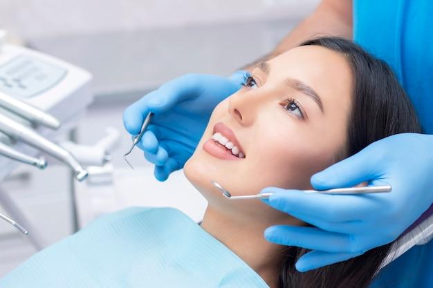 Молодая женщина в стоматологической клинике с стоматологом-мужчиной