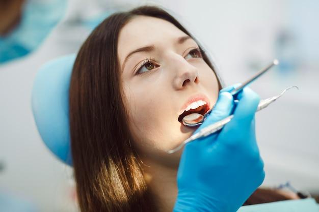 Молодая женщина в стоматологической экзамен