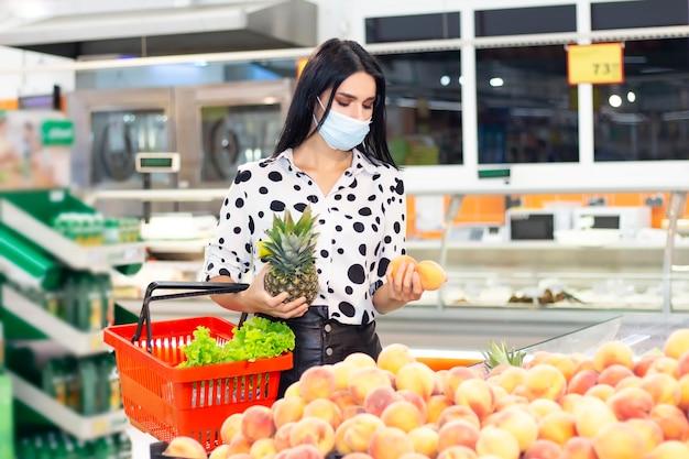 Молодая женщина в одноразовой медицинской маске делает покупки в супермаркете. покупка фруктов