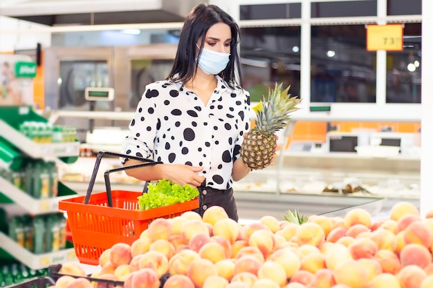 使い捨て医療マスクの若い女性がスーパーマーケットで買い物をしています