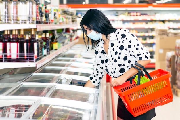 使い捨ての医療用マスクを身に着けた若い女性がスーパーマーケットで買い物をしています。