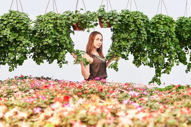 밝은 배경에 꽃과 장식용 암펠러스 식물 사이에서 드레스를 입은 젊은 여성